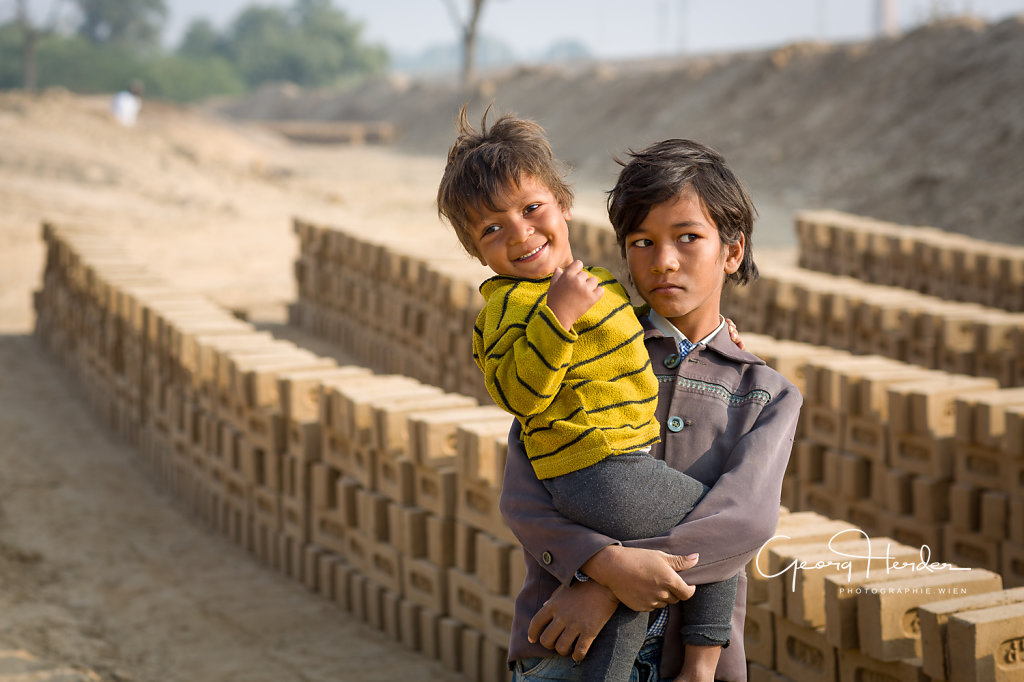 children at a brick mill